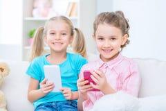 Vrolijke kleine zusters die op de bank zitten Royalty-vrije Stock Afbeeldingen
