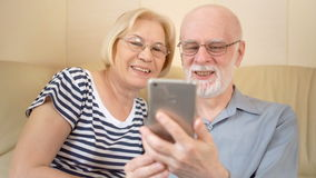 Vrolijke knappe hogere paarzitting op bank thuis Het spreken via Skype op smartphone stock videobeelden
