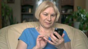 Vrolijke knappe hogere vrouwenzitting als voorzitter thuis Het gebruiken van haar smartphone, het doorbladeren stock videobeelden