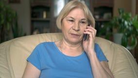 Vrolijke knappe hogere vrouwenzitting als voorzitter thuis Het spreken op haar smartphone stock videobeelden