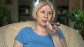 Vrolijke knappe hogere vrouwenzitting op stoel thuis Het spreken op haar smartphone stock video