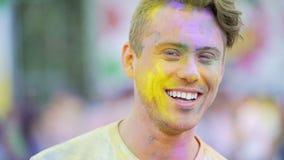 Vrolijke knappe jonge mens die aan camera glimlachen, die aan muziek, gezichtsclose-up dansen stock videobeelden