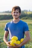 Vrolijke landbouwer die vers meloengewas op het gebied houden bij organisch ecolandbouwbedrijf Royalty-vrije Stock Afbeelding