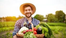 Vrolijke landbouwer met organische groenten stock fotografie