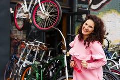 Vrolijke langharige donkerbruine vrouw in een roze kleding bij een fietswinkel royalty-vrije stock fotografie