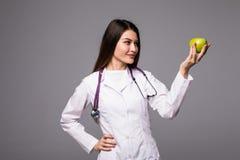 Vrolijke leuke jonge vrouw arts die en een appel over grijze achtergrond bevinden zich houden Stock Foto