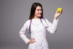 Vrolijke leuke jonge vrouw arts die en een appel over grijze achtergrond bevinden zich houden Royalty-vrije Stock Fotografie