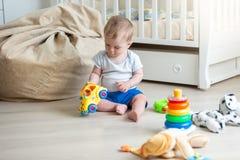 Vrolijke 10 maanden oud baby het spelen op vloer met stuk speelgoed auto en mede Royalty-vrije Stock Foto's