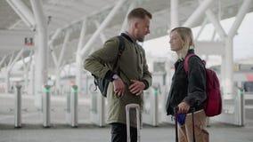 Vrolijke man en vrouw met bagage die zich op post van spoorweg in dag bevinden stock videobeelden