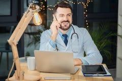 Vrolijke mannelijke arts die zijn mobiele telefoon met behulp van royalty-vrije stock afbeeldingen