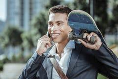 Vrolijke mannelijke student die vrienden met skateboard telefoneren stock afbeeldingen