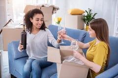 Vrolijke meisjes die glazen voor het drinken van wijn uitpakken stock fotografie