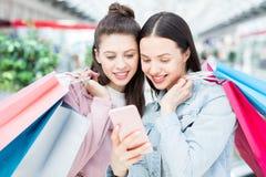 Vrolijke meisjes die het online winkelen app gebruiken stock afbeelding