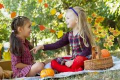 Vrolijke meisjes die pret op de herfstpicknick hebben in park Royalty-vrije Stock Foto