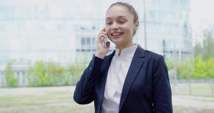 Vrolijke meisjes sprekende telefoon op straat stock videobeelden