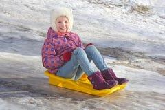 Vrolijke meisjesritten van een ijzige berg op een plastic slee Het kind loopt tijdens de de wintervakantie Stock Foto's