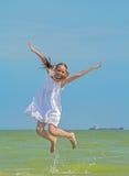 Vrolijke meisjessprongen over het overzees stock fotografie