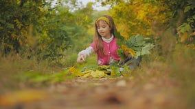 Vrolijke meisjeszitting op het voetpad en het werpen van de herfstbladeren Slow-motion stock video