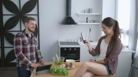 Vrolijke meisjeszitting op lijst en het nemen van beelden grappige kerel op celtelefoon terwijl het koken van nuttige maaltijd vo stock footage