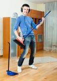 Vrolijke mens die en met borstel in woonkamer spelen schoonmaken Royalty-vrije Stock Afbeelding