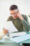 Vrolijke mens die met glazen document lezen Stock Afbeeldingen