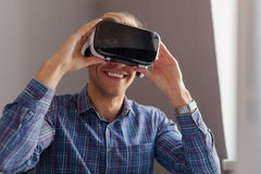 Vrolijke mens die VR-hoofdtelefoon aanpassen Stock Afbeelding