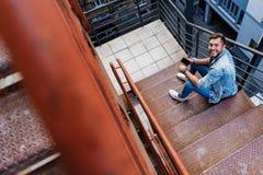 Vrolijke mens met telefoon op trap stock foto's