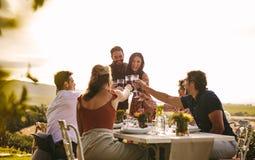 Vrolijke mensen die met dranken bij partij vieren stock afbeeldingen