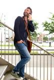 Vrolijke midden oude kerel de treden die mobiele telefoon met behulp van Stock Fotografie