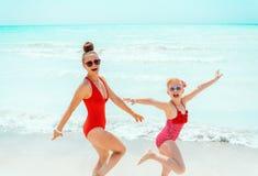 Vrolijke moderne moeder en dochter op zeekust die prettijd hebben royalty-vrije stock fotografie
