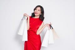 Vrolijke modieuze Aziatische vrouw die een rode kleding met shoppi dragen Royalty-vrije Stock Afbeeldingen