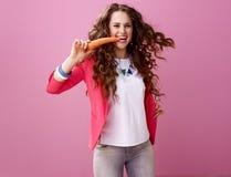 Vrolijke modieuze vrouw die op roze achtergrond wortel eten royalty-vrije stock fotografie