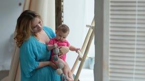Vrolijke moeder die baby ` die s controleren reflex begrijpen stock video