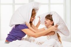 Vrolijke moeder en dochter die hoofdkussenstrijd hebben Royalty-vrije Stock Afbeelding