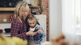 Vrolijke moeder en dochter het doorbladeren smartphone samen en thuis het glimlachen in de ochtend in keuken stock footage