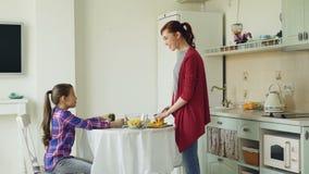 Vrolijke moeder en leuke dochter die en in moderne keuken spreken lachen Scherpe groenten van de mamma de kokende maaltijd Famili stock footage