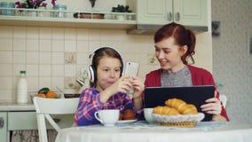 Vrolijke moeder en leuke dochter die ontbijt in de ochtend in keuken hebben thuis Meisje het spelen op smarphone stock video
