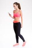 Vrolijke mooie jonge sportvrouw die aan muziek luisteren die smartphone gebruiken Royalty-vrije Stock Foto