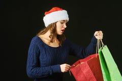 Vrolijke mooie jonge vrouw in hoed van Santa Claus met pakketten op een donkere achtergrond Stock Foto's