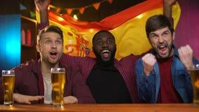 Vrolijke multiraciale mannelijke ventilators die voor Spaanse sporten team, golvende vlag toejuichen stock videobeelden