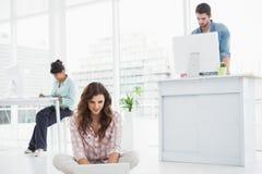 Vrolijke onderneemsterzitting op de vloer die laptop met behulp van Royalty-vrije Stock Foto's