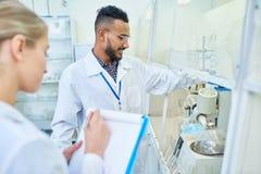 Vrolijke onderzoeker en zijn medewerker die laboratoriummateriaal met behulp van royalty-vrije stock afbeelding