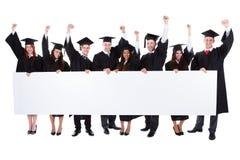 Vrolijke opgewekte gediplomeerde studenten die lege banner tonen stock afbeeldingen