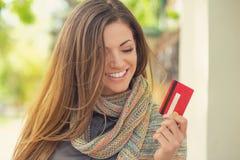Vrolijke opgewekte jonge vrouw met creditcard die zich in openlucht bevinden stock afbeeldingen