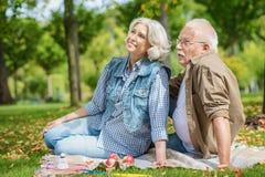 Vrolijke oude echtgenoot en vrouw die in park rusten stock foto's