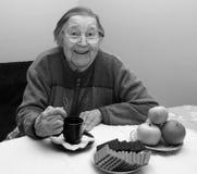 Vrolijke oude grootmoeder het drinken thee Stock Afbeelding