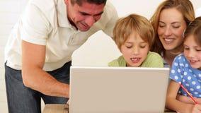 Vrolijke ouders en kinderen die kunsten en ambachten samen met laptop doen stock video