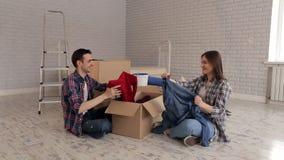 Vrolijke paar uitpakkende dozen die op de vloer in zijn nieuwe flat zitten stock footage