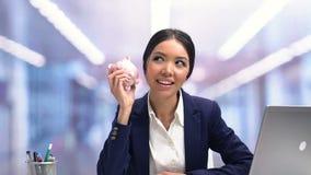 Vrolijke piggybank en dame die, voordelige investering voor toekomst schudden glimlachen stock video