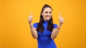 Vrolijke positieve en blije vrouw die duimen op oranje yelowachtergrond tonen stock videobeelden